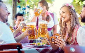 Couple clinking glasses with huge amounts of beer in Bavarian pub