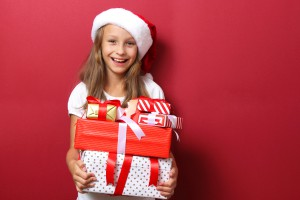 cute cheerful girl in a Christmas hat on a colored background holding gifts in her hands